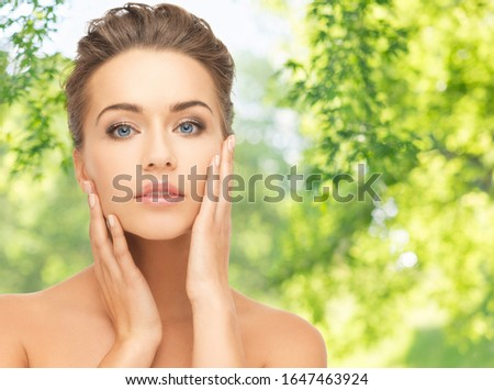 people, beauty and skin care concept - face of beautiful woman over green natural background