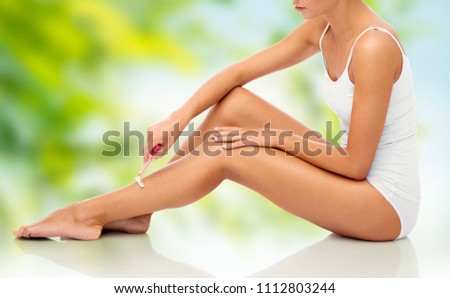 people, beauty, depilation and bodycare concept - beautiful woman with safety razor shaving legs sitting on floor over green natural background #1112803244