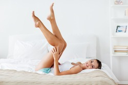 people, beauty, depilation, epilation and bodycare concept - beautiful woman lying on bed and touching smooth leg skin at home bedroom