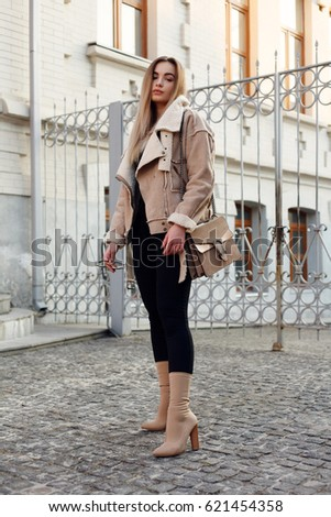 People, beauty, fashion, lifestyle and color concept - Outdoor full body portrait of young beautiful happy smiling girl posing on street. Model looking at camera. Lady wearing stylish winter clothes #621454358