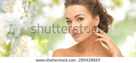 people, beauty, jewelry and accessories concept - beautiful woman with diamond earrings over summer garden and cherry blossom background