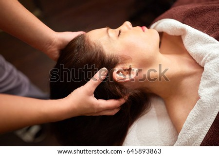 people, beauty, lifestyle and relaxation concept - beautiful young woman lying with closed eyes and having head massage at spa #645893863