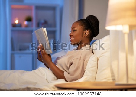 people, bedtime and rest concept - young african american woman reading book in bed at home at night Photo stock ©