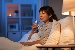 people, bedtime and thirst concept - happy smiling asian woman drinking water at night in bed at home