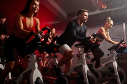 people biking in spinning class at modern gym, exercising on stationary bike. group of caucasian people athletes training on exercise bike