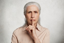 People, body language concept. Old female model keeps fore finger on lips, asks to be silent as has headache, dressed in elegant shirt, isolated over white background. Pensioner gestures indoor