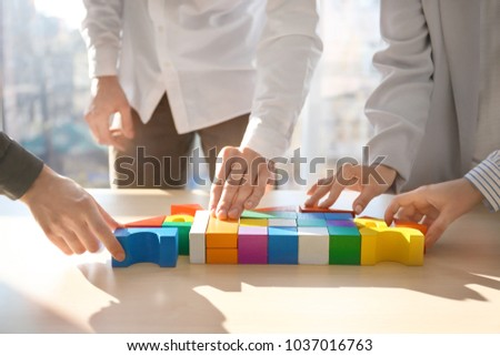 People building house together on table, closeup. Unity concept #1037016763