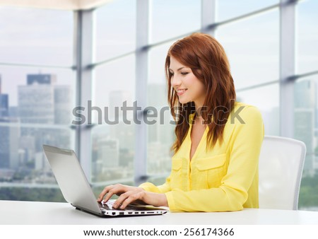 people, business and technology concept - smiling young woman with laptop computer sitting at table over office window background