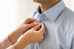 people, business, care and clothing concept - close up of woman helping man and fastening buttons on his shirt at home