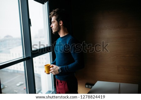 People, business, fashion and style concept. Young European male freelancer with fuzzy hairstyle and brisile, looking at the big window in modern living room, holding in hands a cup of coffee