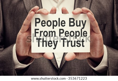 People Buy From People They Trust. Businessman holding a card with a message text written on it #353671223