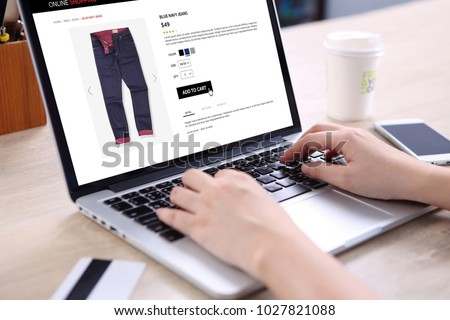 People buying blue navy jeans on ecommerce website with smart phone, credit card and coffee on wooden desk #1027821088