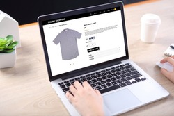 People buying casual shirt on ecommerce website with smart phone on wooden desk
