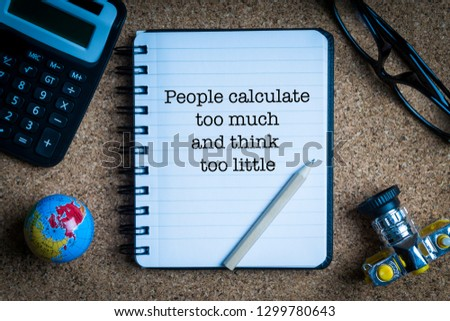PEOPLE CALCULATE TOO MUCH AND THINK TOO LITTLE inscription written on book with globe,eyeglasses, calculator, camera, pencil and vase on wooden background. Business and education concept Stock fotó ©