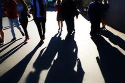 People casting shadows on a street in Helsinki