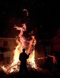 People celebrate St John's Eve around a bonfire in a greek village