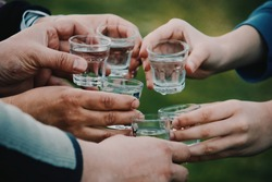 people celebrating and toasting with shots of alcohol vodka outdoors
