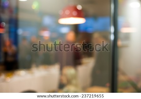 People celebrating dining in cafe through window glass background bokeh