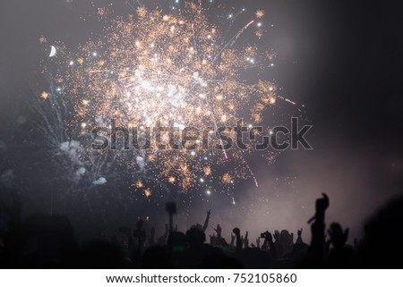People celebrating New Year's eve with raised up hands. Fireworks and light. New Year's eve concept.