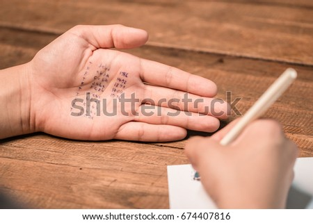 People cheating on test by writing answer on hand #674407816