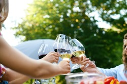 People Cheering With Drinks At Outdoor Dinner Party. Close Up Of People Hands Raising Toast With Glasses Of Wine, Enjoying Outdoor Picnic In Nature. High Quality Image.