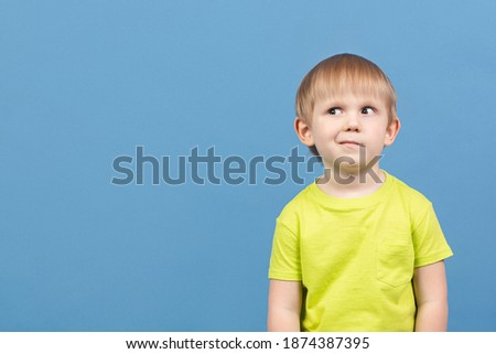 People child looks away, face expresses doubt, disbelief, curiosity, dilemma, guesswork, imagination, planning and mischief. Cunning kid skeptic suspects something. Studio shot with copy space. Stock photo ©