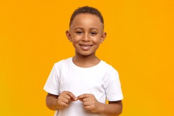 People, childhood, school age and lifestyle concept. Horizontal studio image of handsome adorable African American schoolboy dressed in white t-shirt, looking at camera with broad happy smile