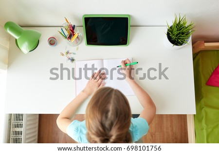 people, children and education concept - girl with tablet pc computer writing to notebook at home