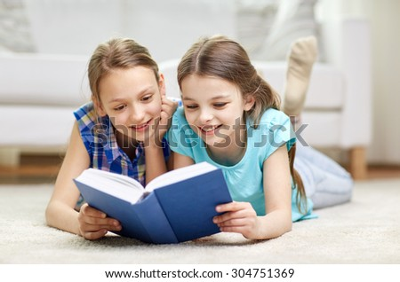 people, children, friends, literature and friendship concept - two happy girls lying on floor and reading book at home