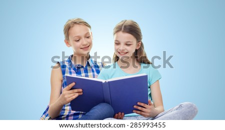 people, children, friends, literature and friendship concept - two happy girls sitting and reading book over blue background