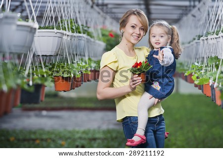 people - children, gardening and occupation concept - happy children taking care of the flowers in the greenhouse. Mom showing baby flowers and playing with your child