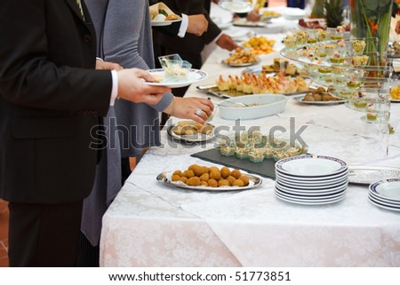 People choosing food from buffet during a wedding ceremony