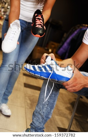 People choosing sports footwear in sport outlet