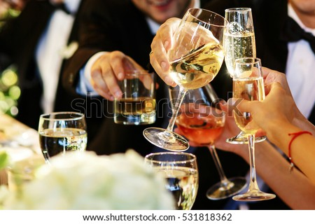 People clang glasses sitting at dinner table in sparkling lights