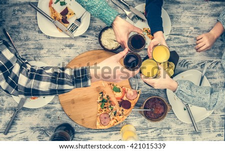 people clanging glasses together having pizza top view