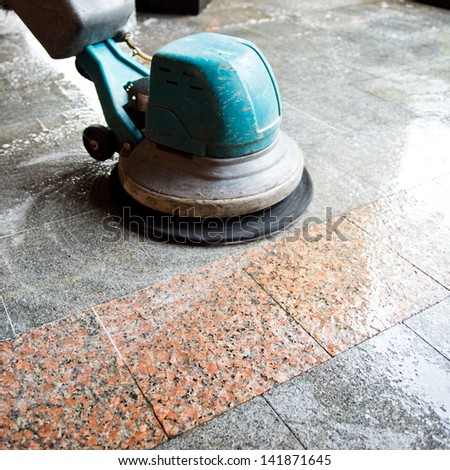 People cleaning floor with machine.
