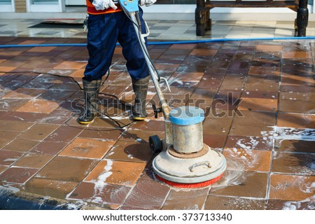 People cleaning floor with machine