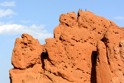 people climb to the top of a huge rock summit, successful people acheiving their goal