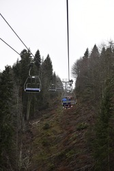 People climb up to the TV tower on the bench of the old ski lift above the forest