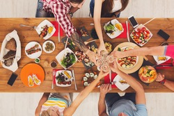 People clink glasses, saying cheers, eat healthy meals at party dinner table. Friends celebrate with organic food, ratatoille and corn barbecue on wooden table top view. Woman pass dish plate to man