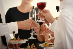 People clinking glasses at buffet catering party, close up view