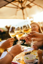 People clinking glasses with wine on the summer terrace of cafe or restaurant