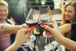 People clinking glasses with wine on the summer terrace of cafe or restaurant. Happy cheerful friends celebrate summer or autumn fest. Close up shot of human hands, lifestyle.