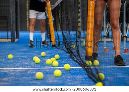 People collectoring balls on a padle or tennis court Stock fotó ©