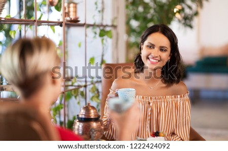 people, communication and friendship concept - female friends drinking coffee and talking at cafe