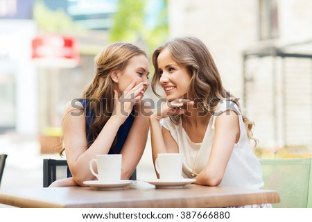 people, communication and friendship concept - smiling young women drinking coffee or tea and gossiping at outdoor cafe