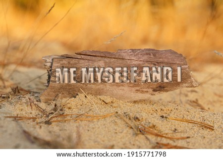 People concept. On the sand against a background of yellow grass, a signboard with the inscription - ME MYSELF AND I Сток-фото ©