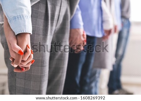 People connection. Group of millennials holding hands of each other during psychological group therapy session, free space