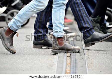 People crossing street, close up of feet. Tram rails