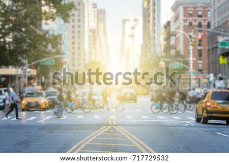 People crossing the busy intersection between traffic on 3rd Avenue and 10th Street in Manhattan in New York City with the glow of sun light in the background #717729532